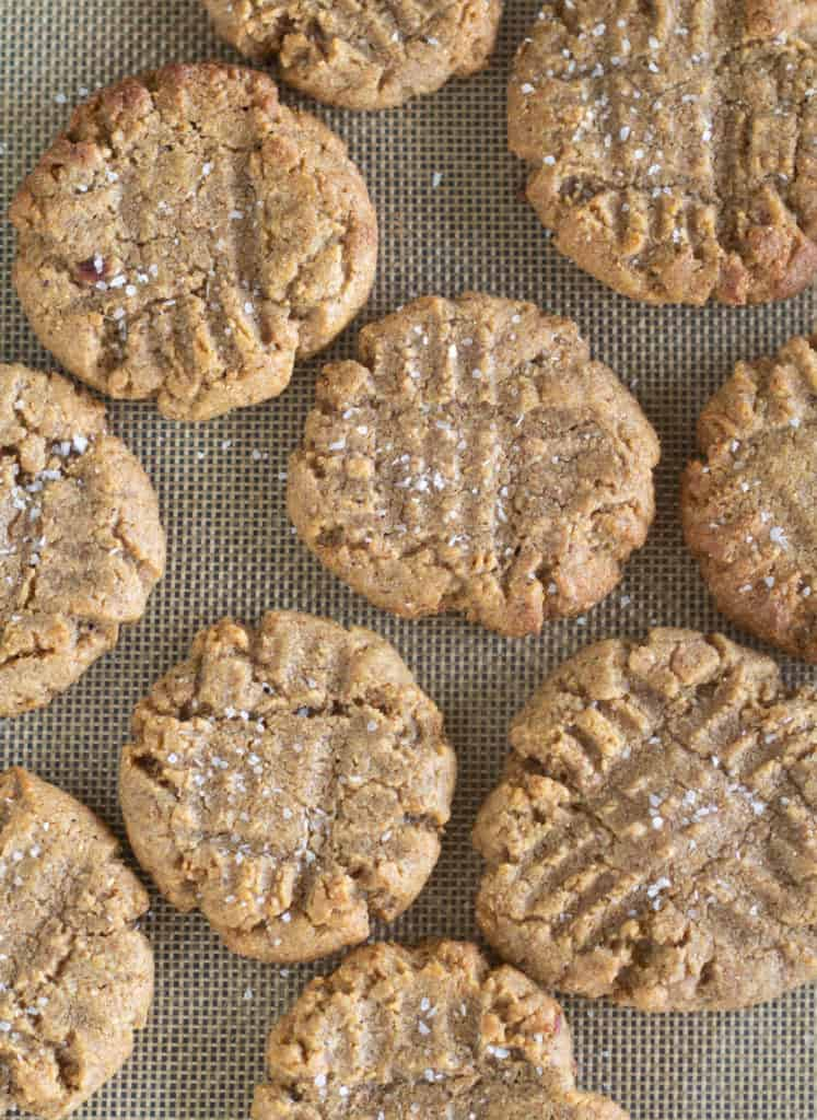 Overhead shot of Baked Keto Peanut Butter Cookies on baking sheet with sea salt sprinkled on the top