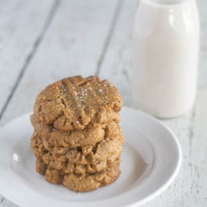 Flourless Keto Peanut Butter Cookies stacked on a small white plate with milk in the background