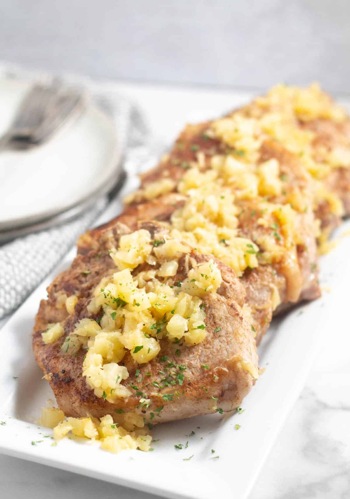 pork chops with chopped pineapple on white platter