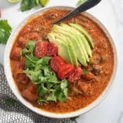 taco soup topped with avocado, cilantro, and tomatoes