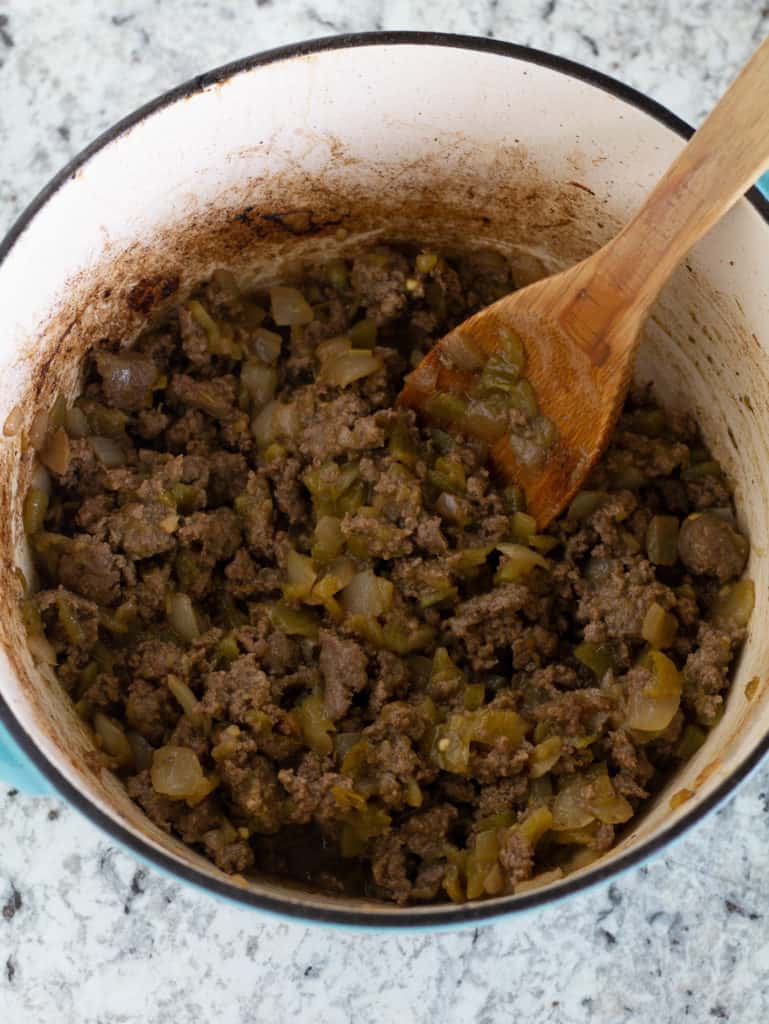 Cooked beef with green chiles in large pot