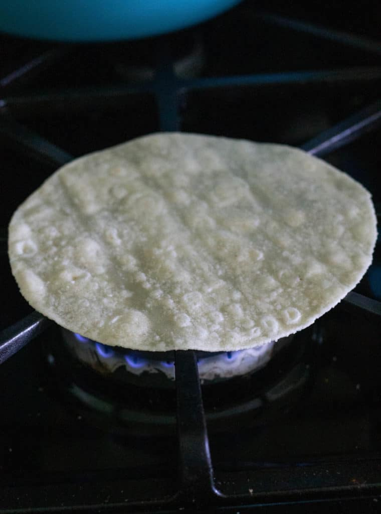 Paleo tortilla being heated on gas stove