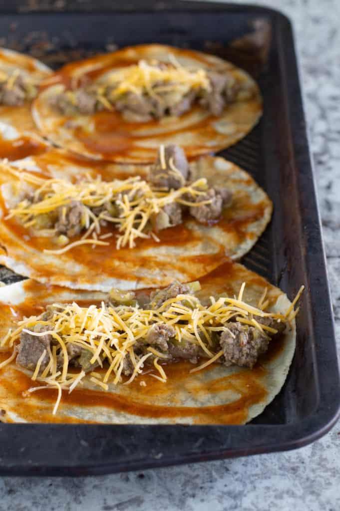 Unbaked enchiladas on baking sheet
