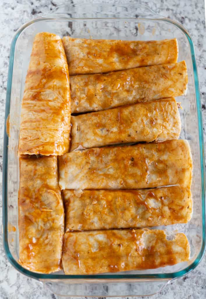 rolled and unbaked paleo and keto beef enchiladas in baking dish