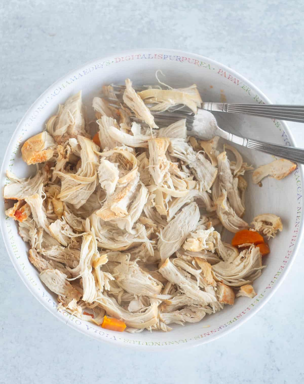 shredded chicken in large white bowl