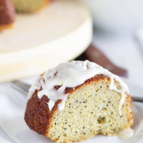 piece of keto lemon poppy seed bundt cake on white plate with glaze