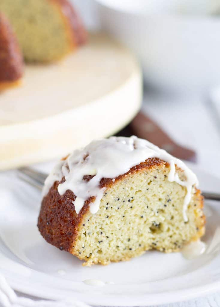 piece of keto lemon poppy seed bundt cake on white plate with glaze