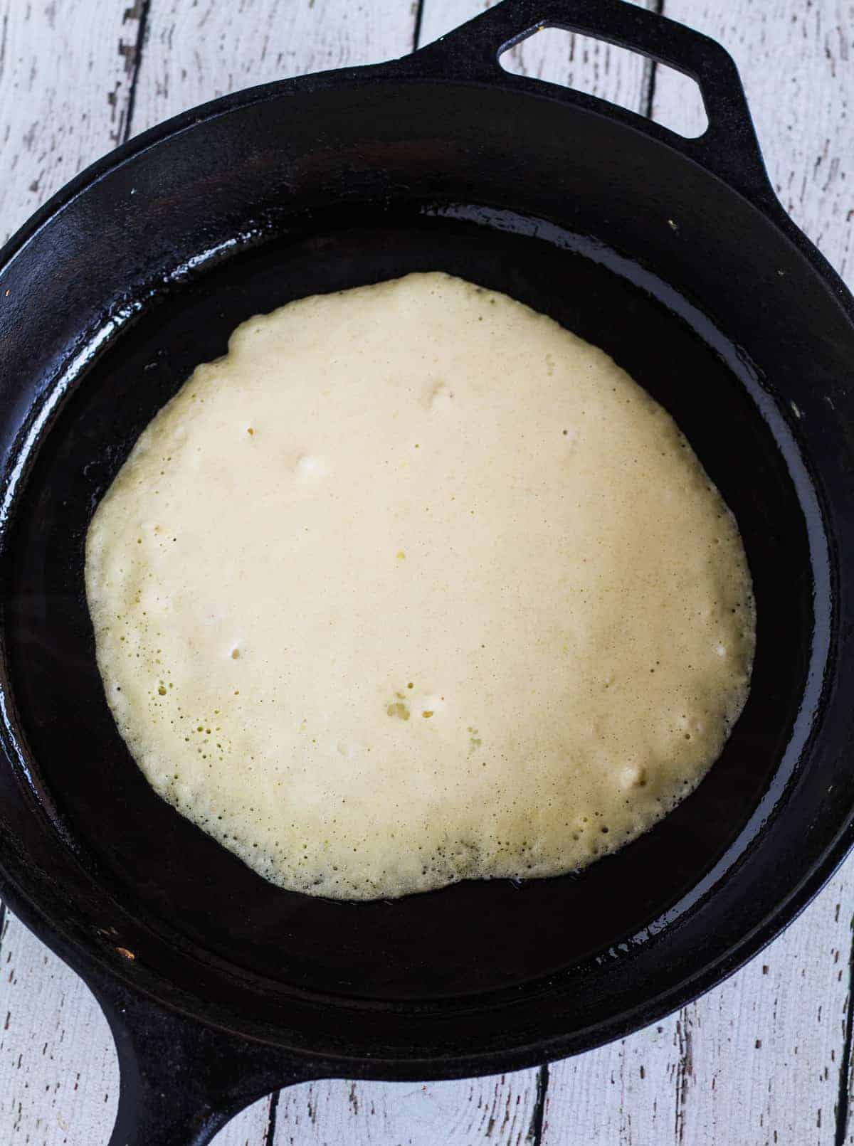 batter cooking in cast iron skillet