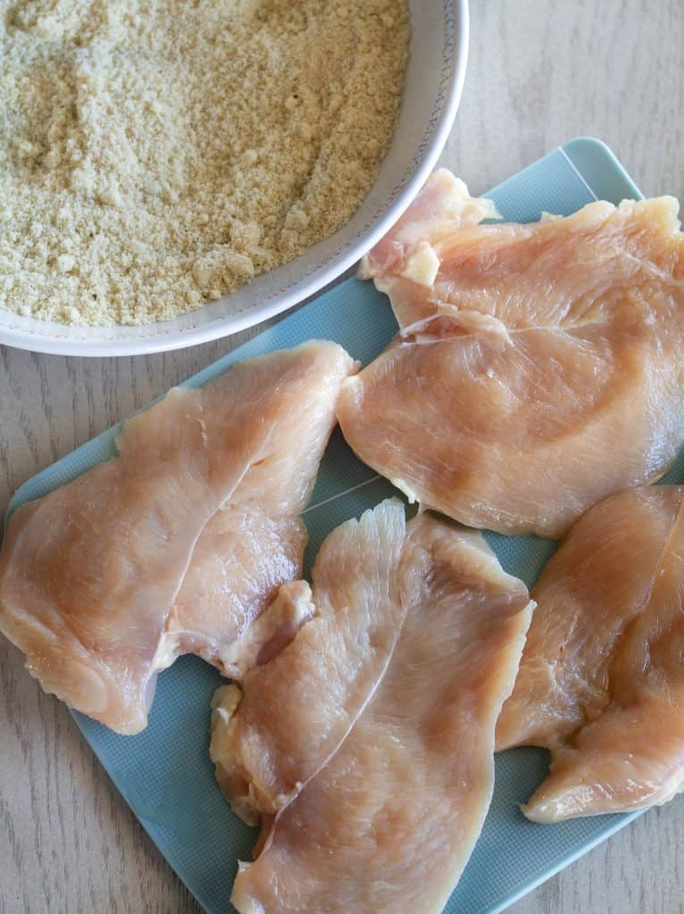 Uncooked Chicken Breasts With A bowl of seasoned almond flour