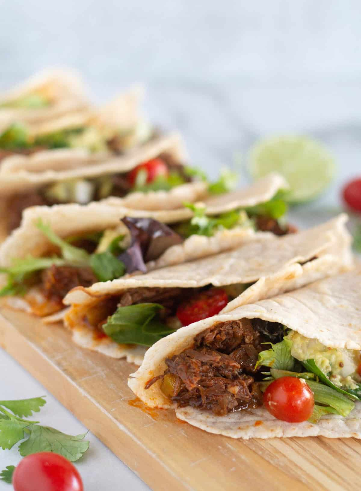 close up of shredded beef tacos on cutting board