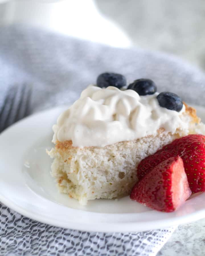 Keto Angel Food Cake with whipped cream and berries on white plate
