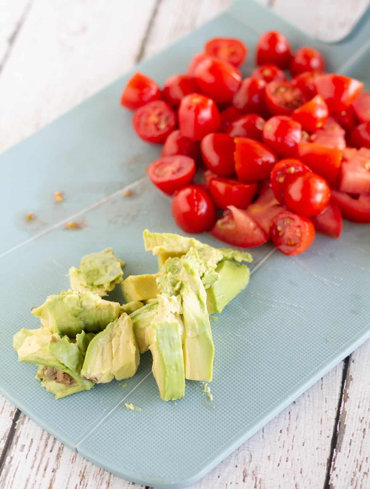 chopped tomatoes and avocado on cutting board