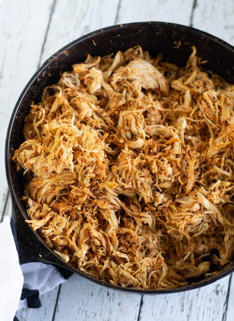 cooked chicken with taco seasonings in a cast iron skillet