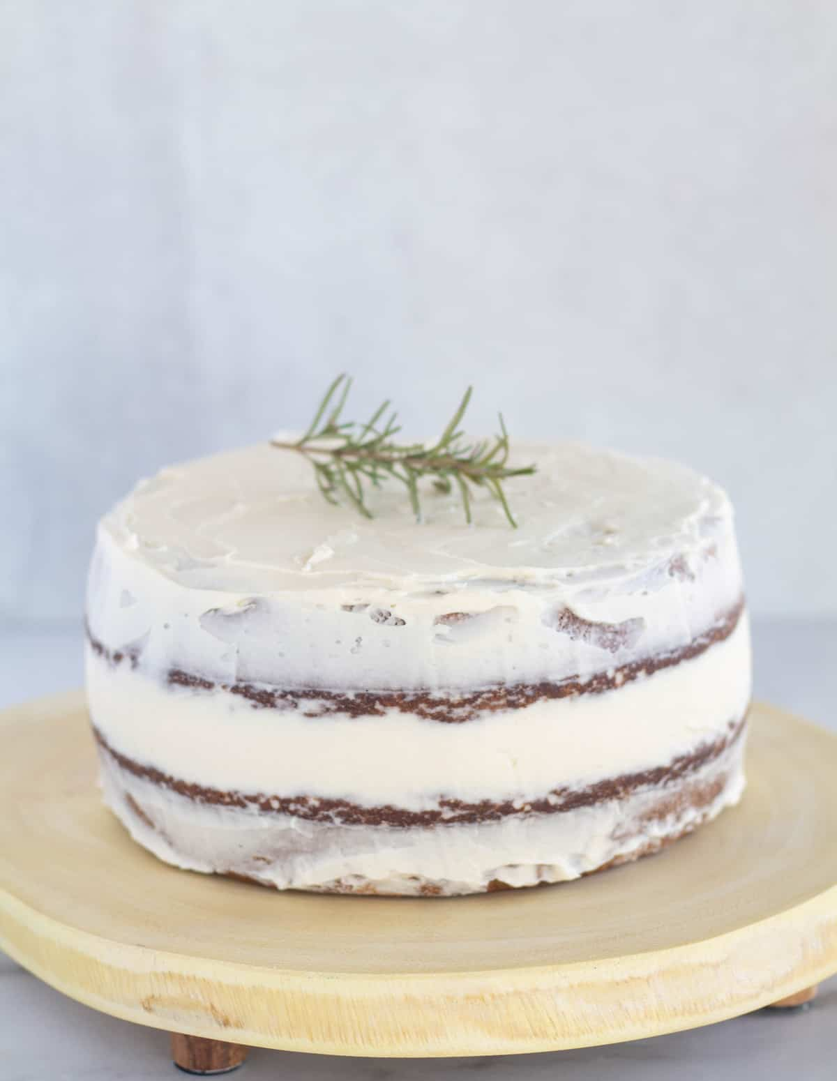 frosted cake on cake plate with rosemary