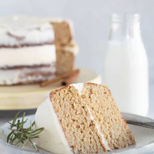 slice of keto gingerbread cake on plate with rosemary