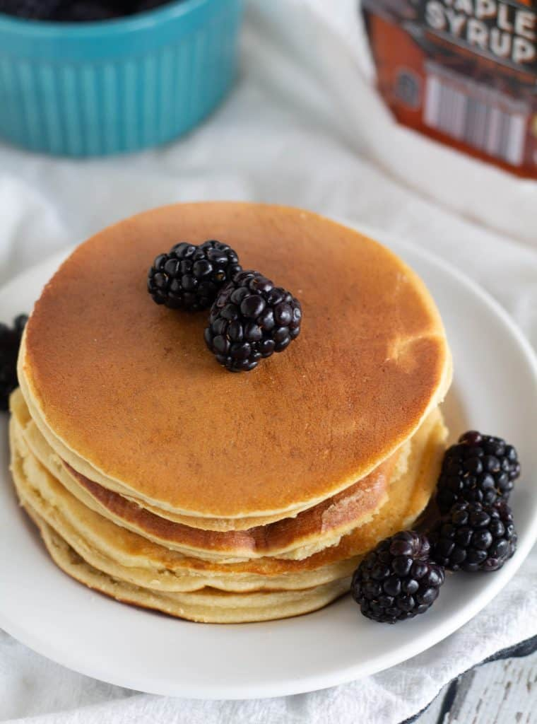 almond flour pancakes stacked on white plate with blackberries