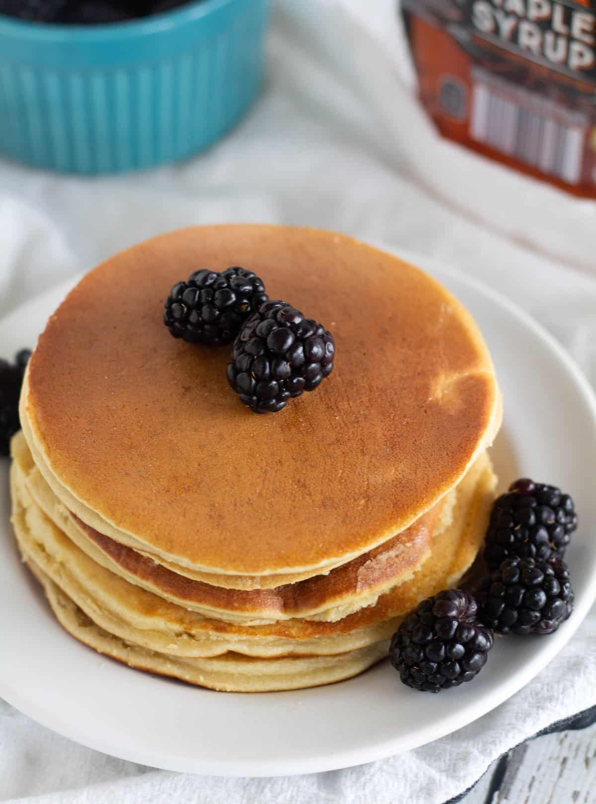 pancakes stacked on white plate with blackberries
