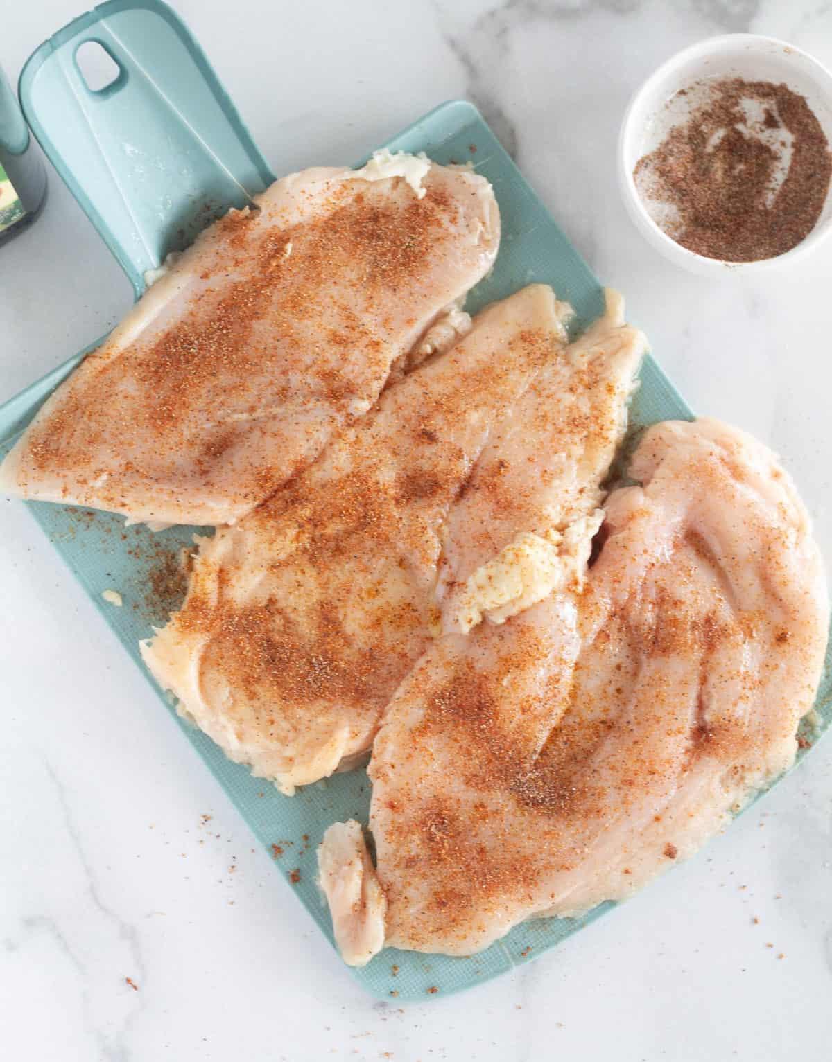 seasoned chicken on cutting board
