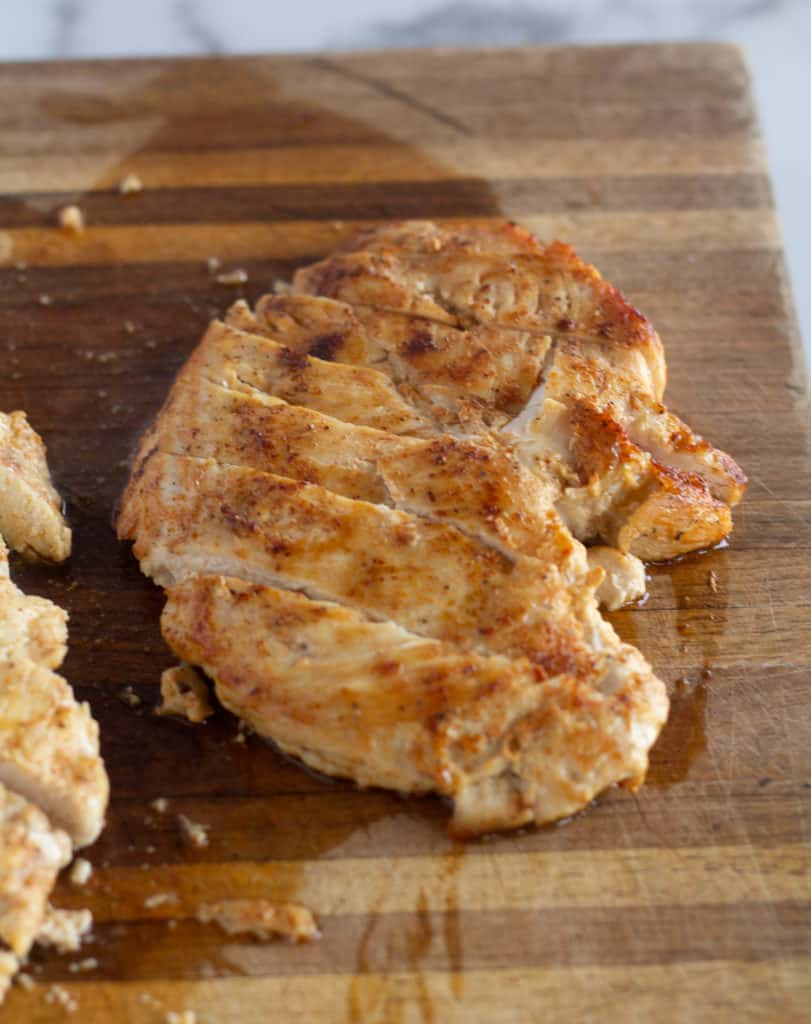 grilled and sliced chicken on cutting board