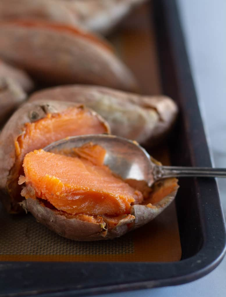 scooping out the flesh of a baked sweet potato