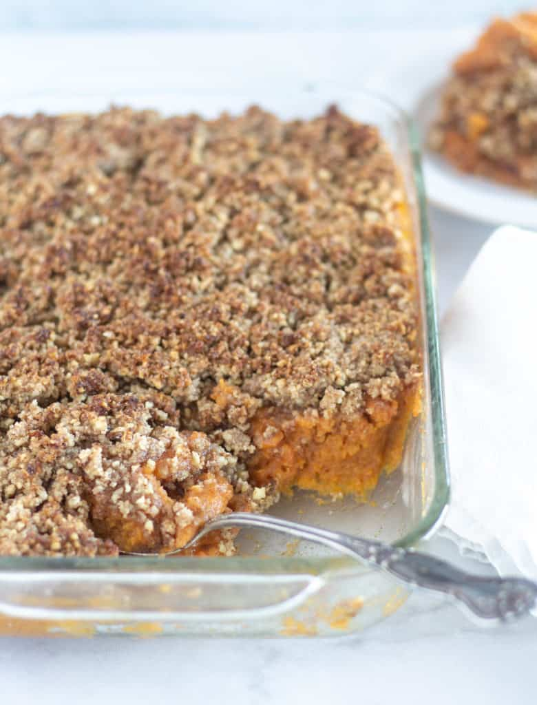 scooping out healthy sweet potato casserole onto a white plate
