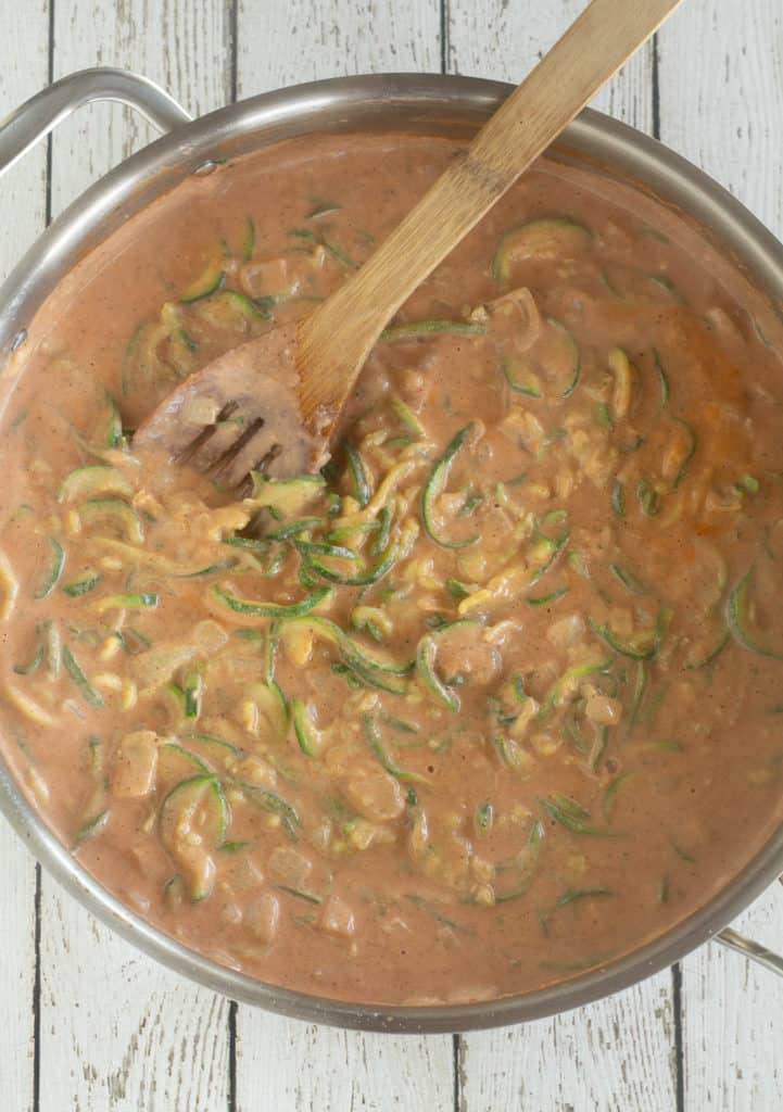 Zucchini noodles with tomato based cashew sauce in a large pan