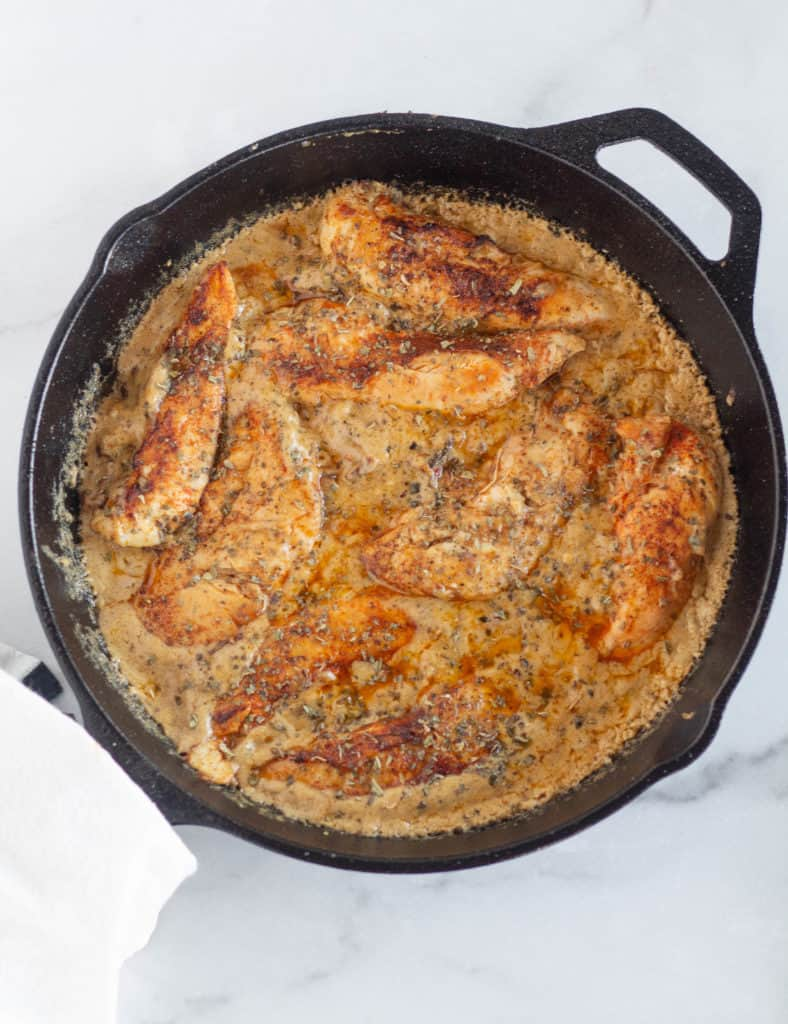 overhead shot of chicken in sun dried tomato cream sauce in cast iron skillet