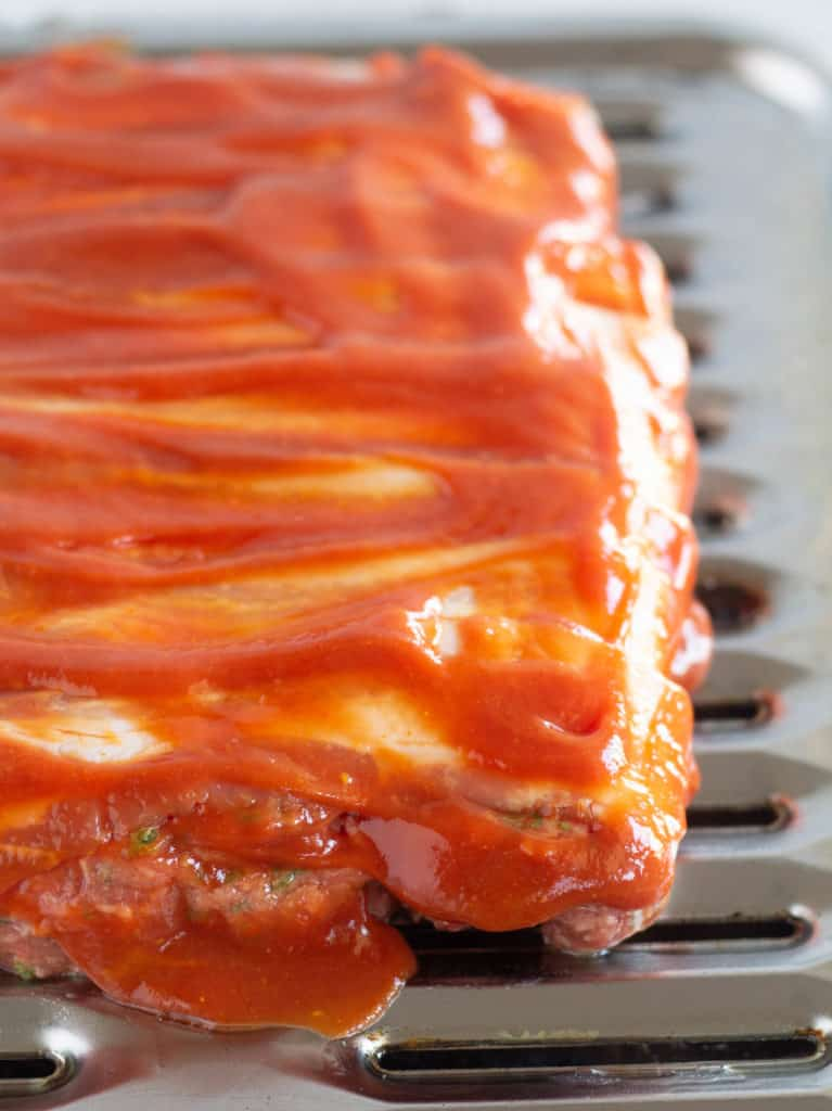 bacon wrapped meatloaf with ketchup gravy on broiler pan