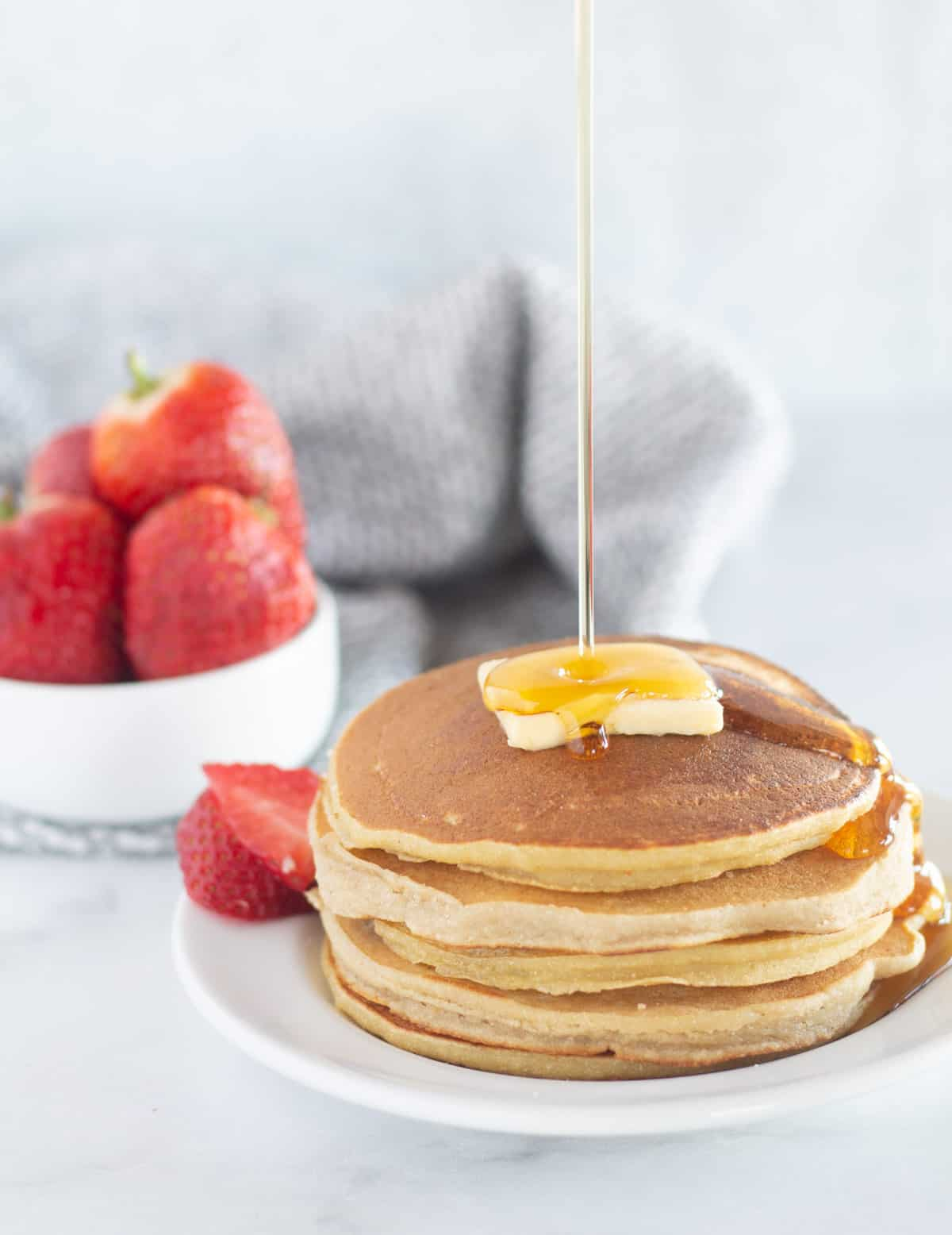 stack of cassava flour pancakes with strawberries and maple syrup