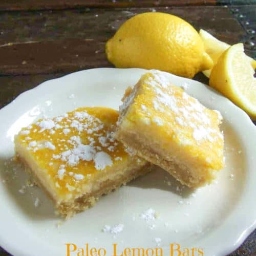 2 paleo lemon bars on white plate with lemons