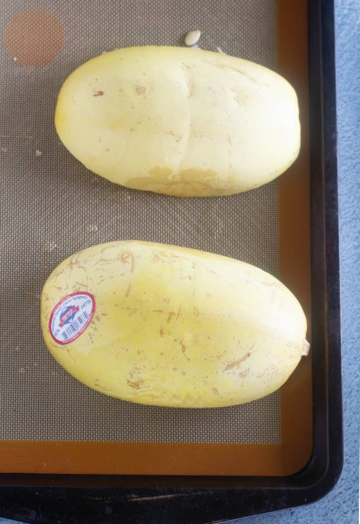 Spaghetti Squash cut in half flesh side down on a silpat lined baking sheet
