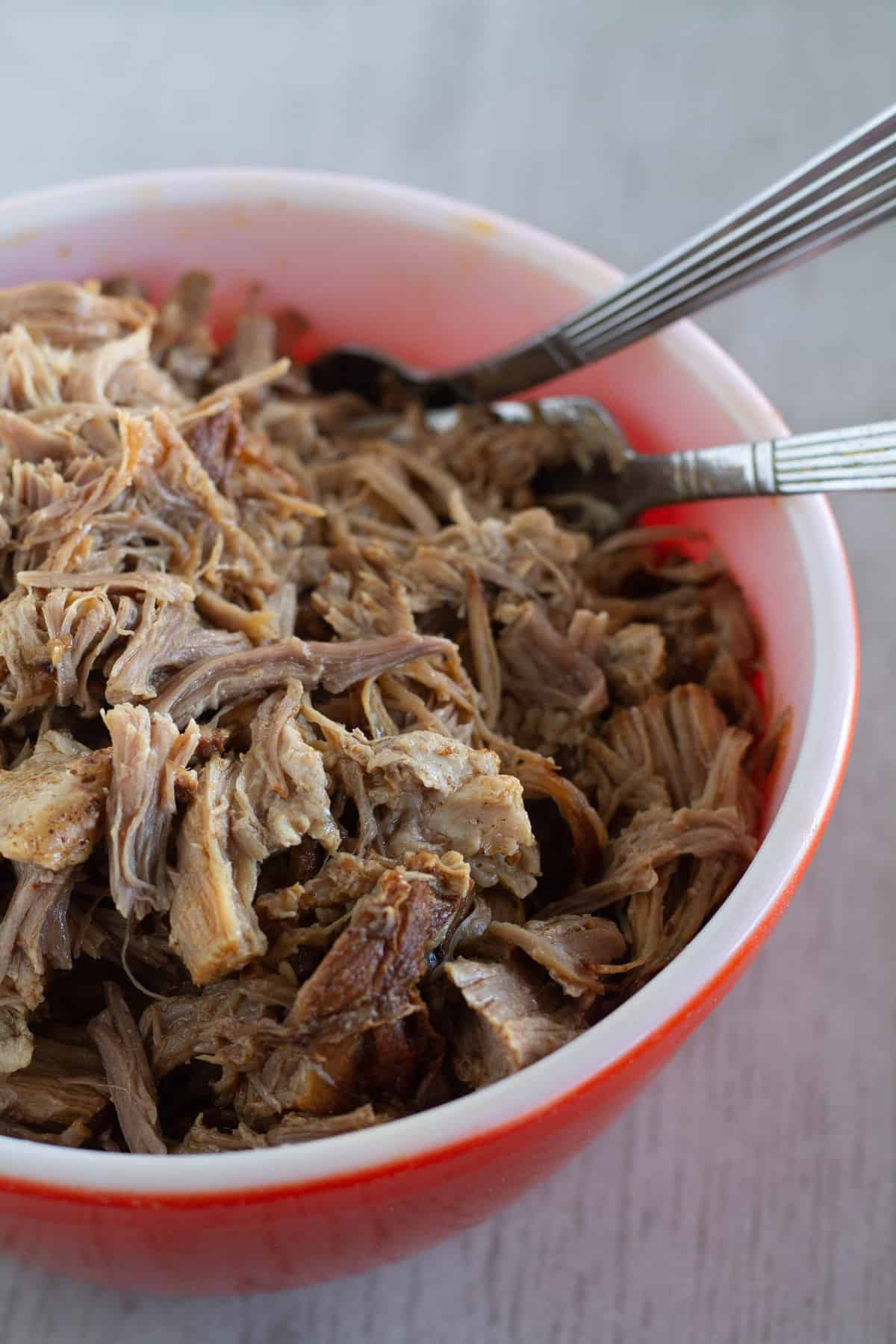 Cooked pulled pork in a bowl with 2 forks