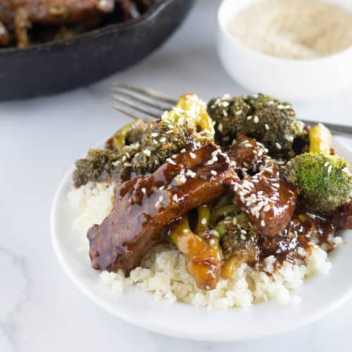 paleo beef and broccoli over cauliflower rice on white plate