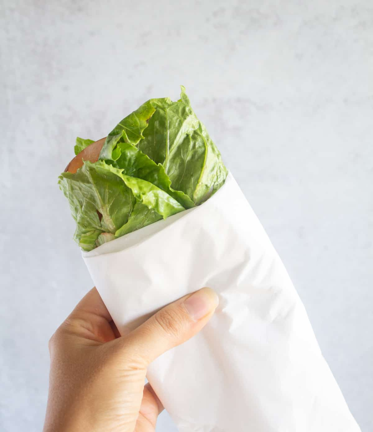 holding up a lettuce wrapped sandwich