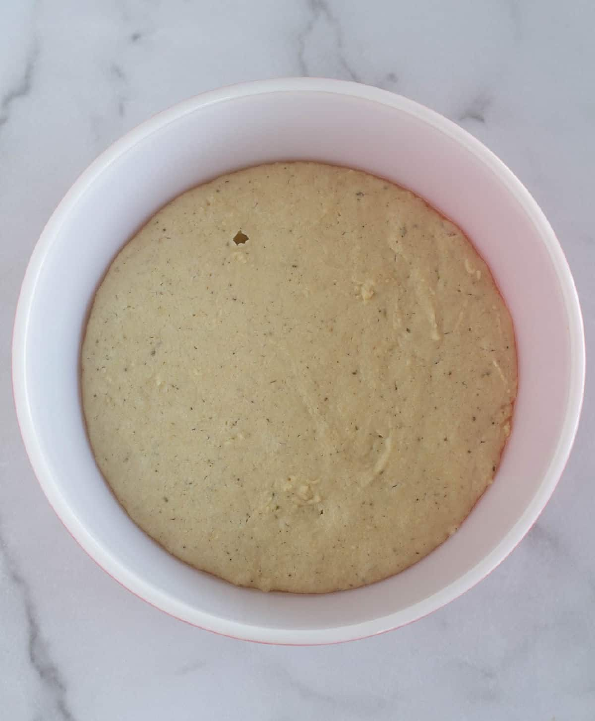 pizza dough in bowl after rising