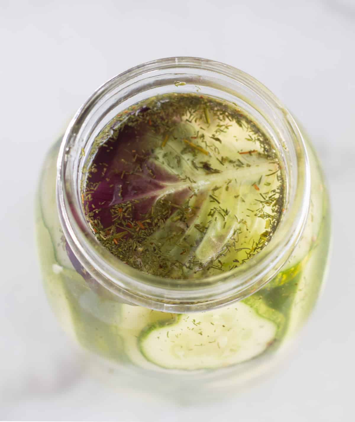 overhead shot of lettuce leaf in the top of a mason jar over the pickles