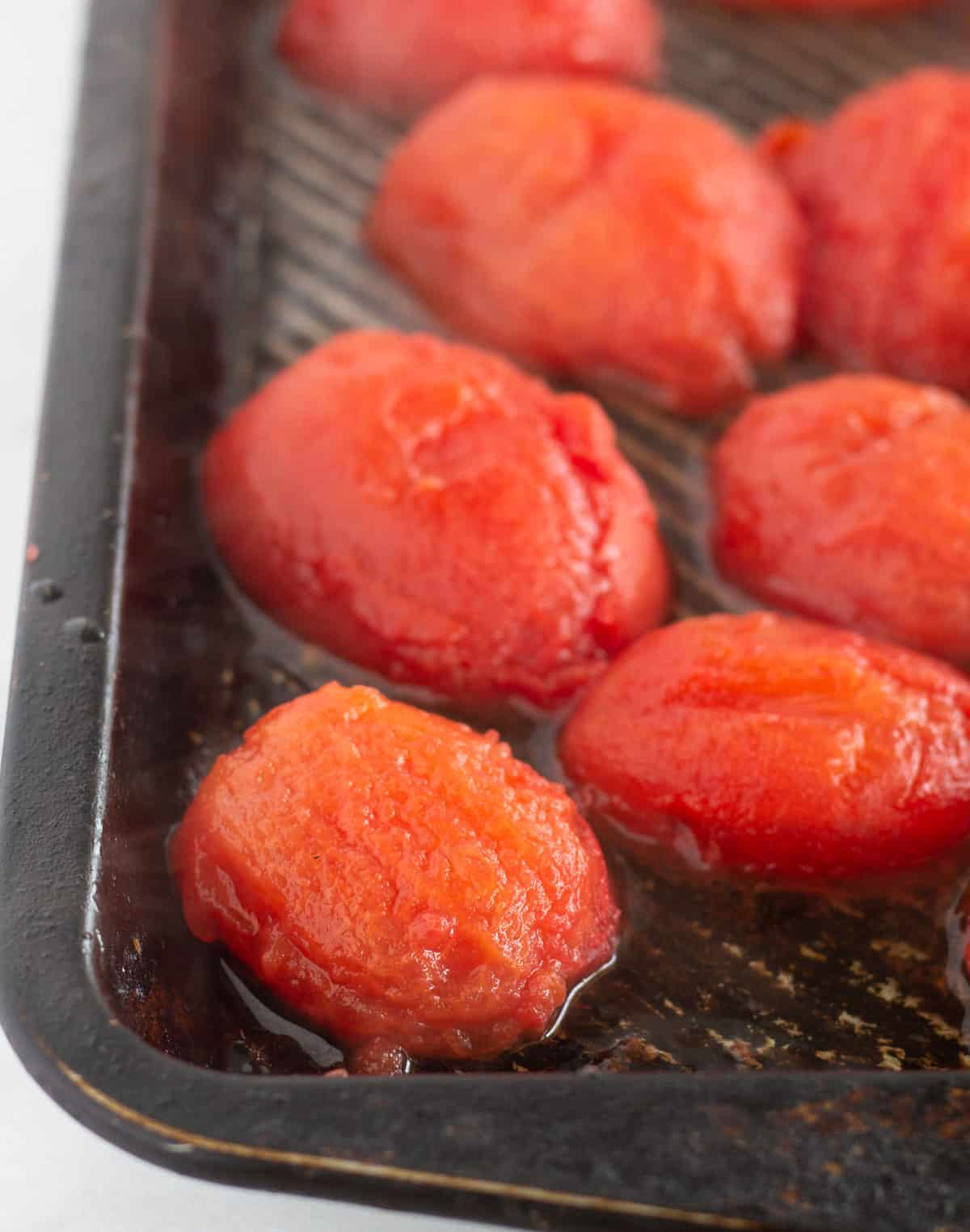 peeled tomatoes on baking sheet