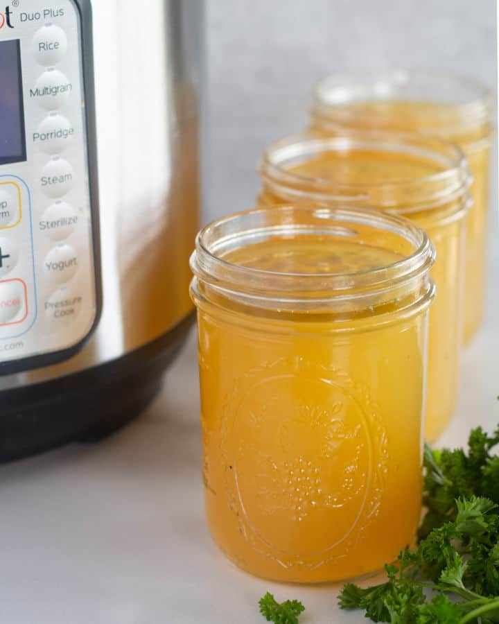 instant pot bone broth in mason jars with an instant pot in the background