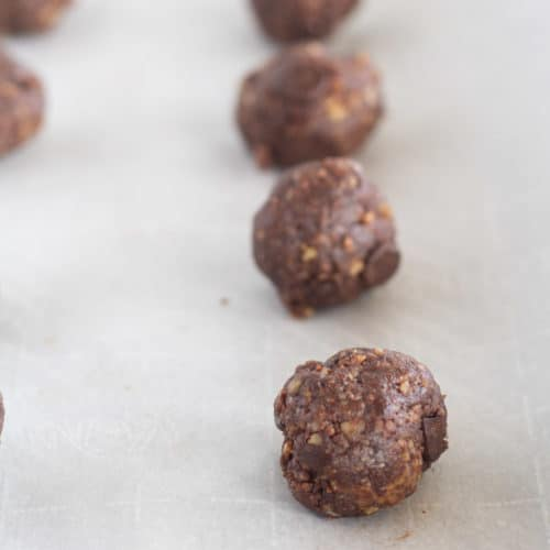 dough rolled into balls on parchment-lined baking sheet