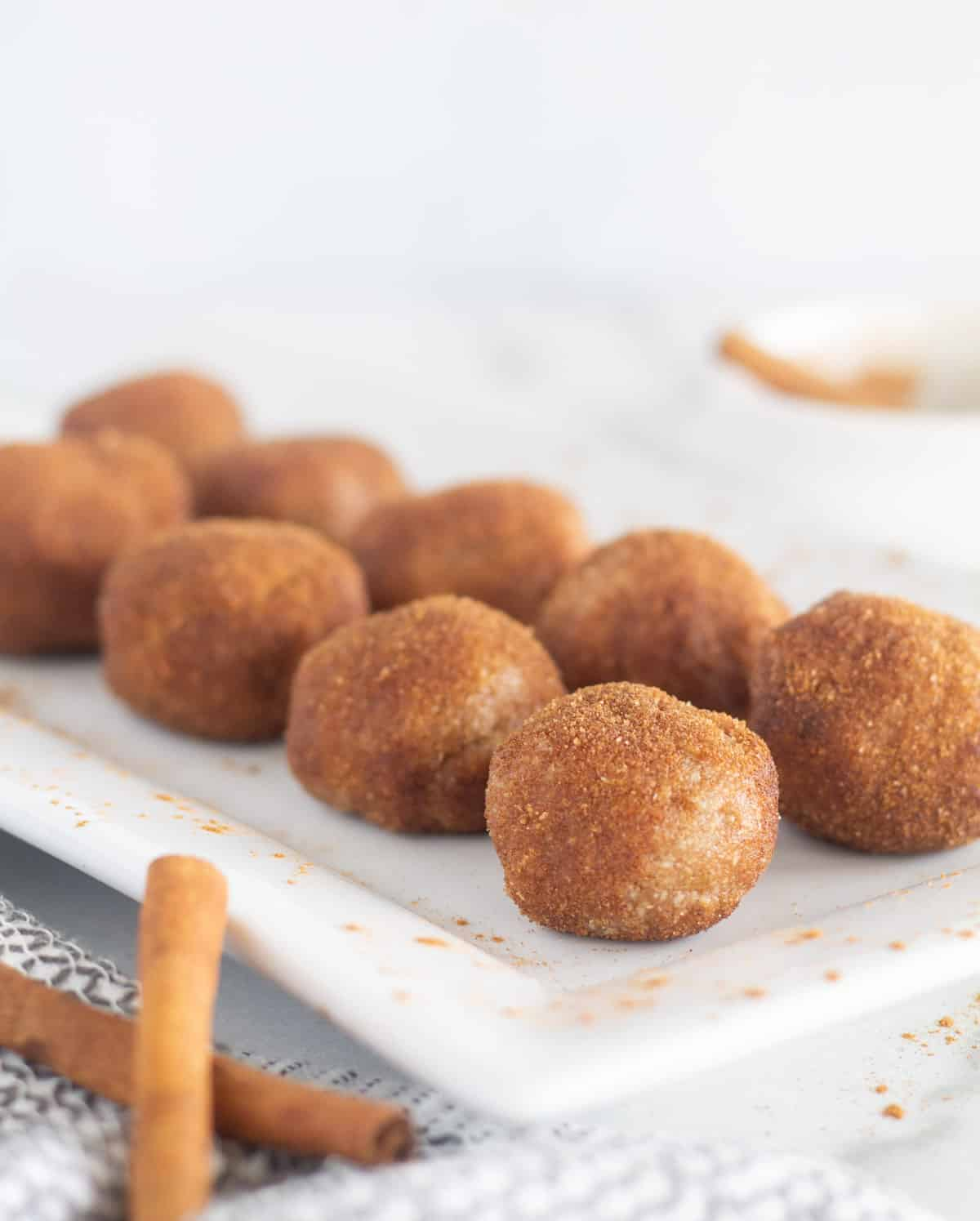 close up of donut holes on white plate