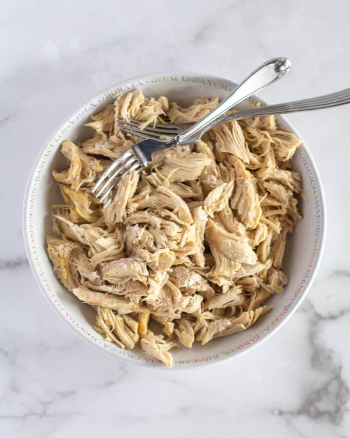 overhead shot of shredded chicken in a white bowl