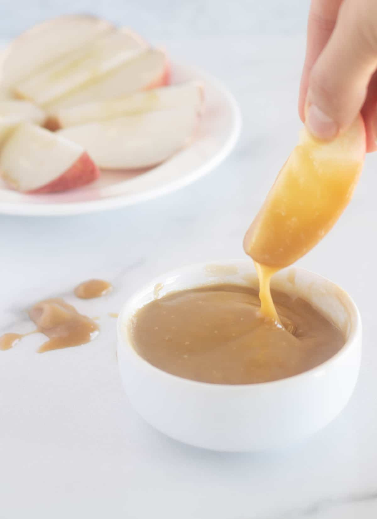 dipping an apple into caramel sauce