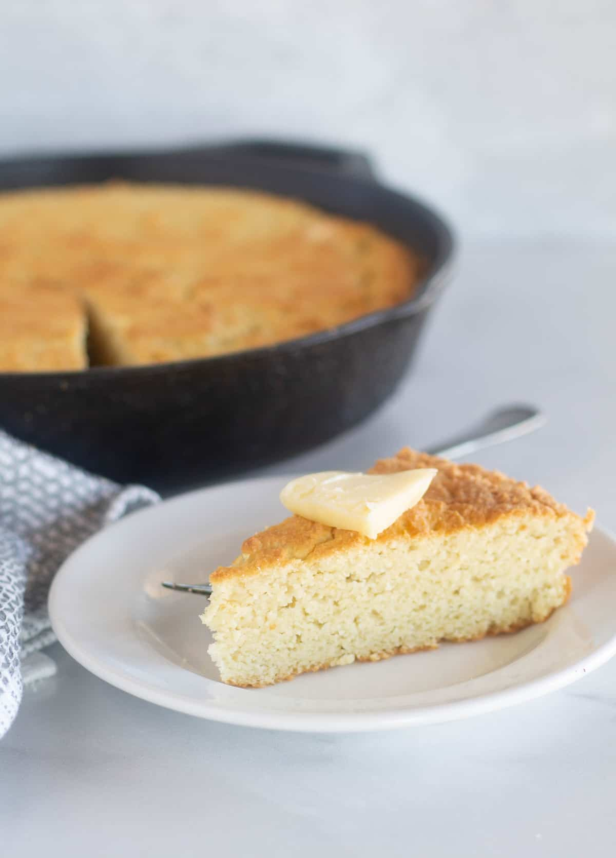 close up of cornbread on a white plate