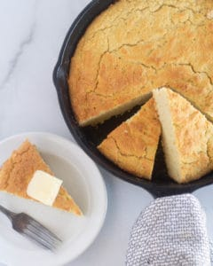 overhead shot of cornbread in cast iron skillet with 1 piece on a white plate