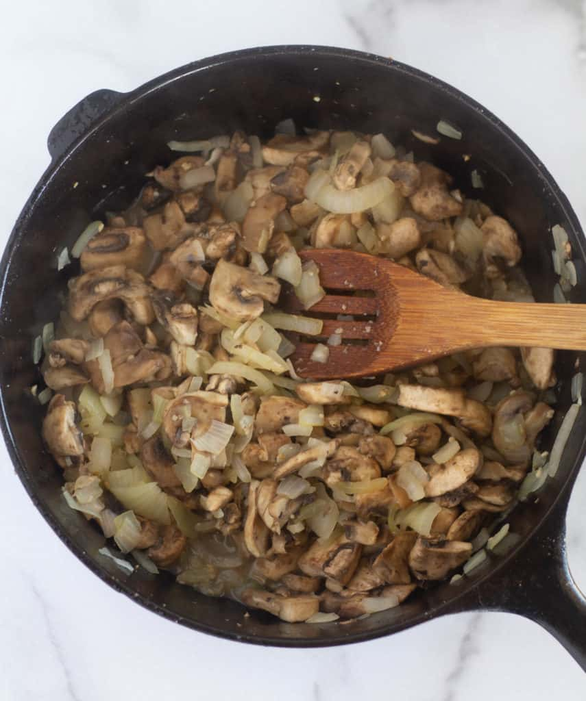 cooked mushrooms and onion in cast iron skillet