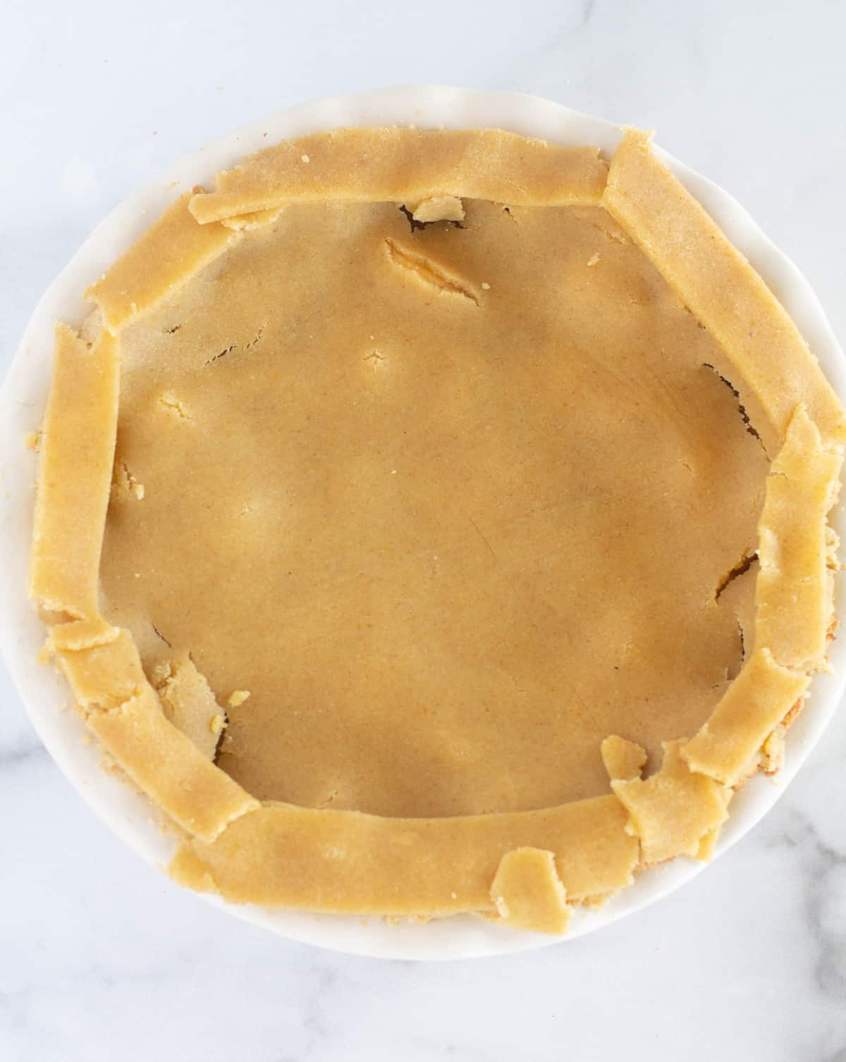 apple pie with unbaked top crust and strips of crust around the edge