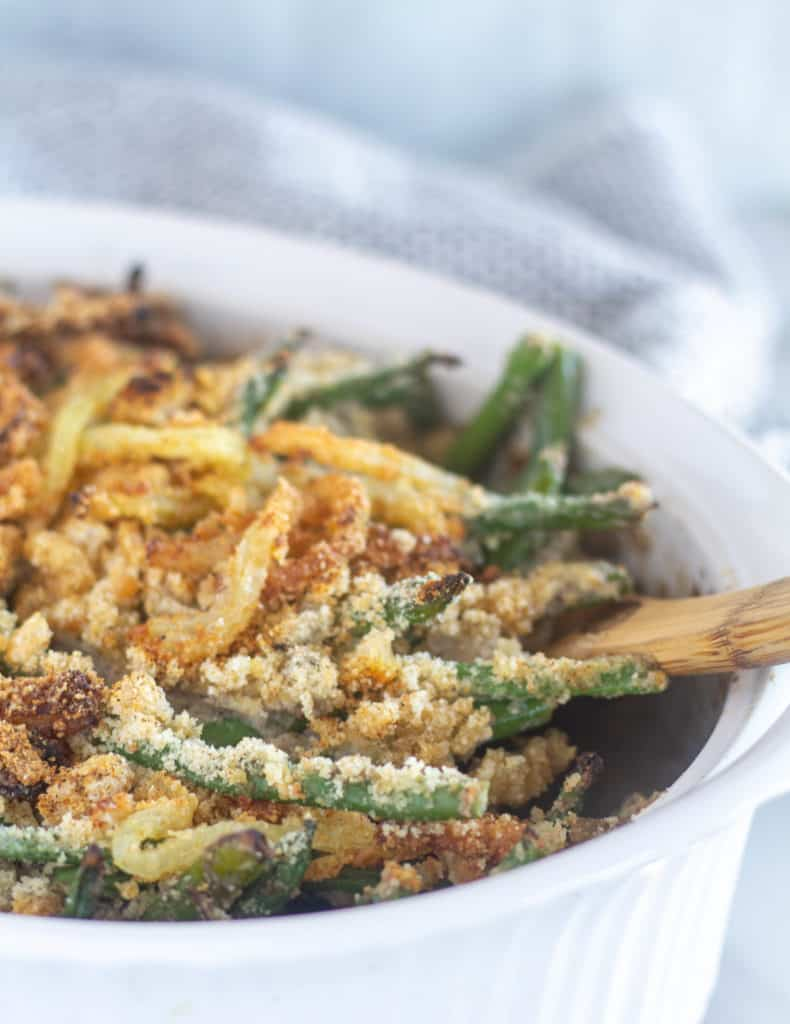 side shot of green bean casserole in baking dish with a wooden spoon