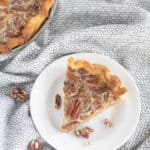 overhead shot of piece of keto pecan pie on a white plate