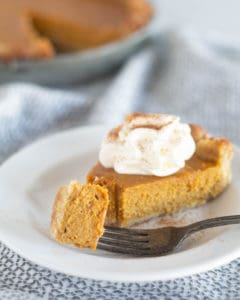 piece of paleo and keto pumpkin pie on white plate with whipped cream