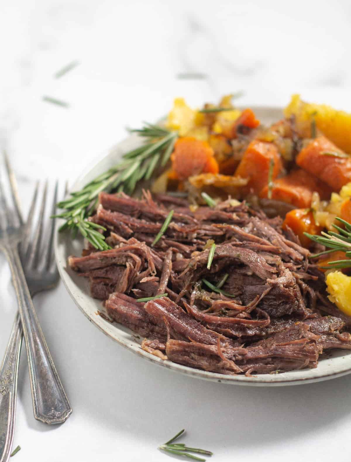close up of shredded roast on a plate with carrots and potatoes